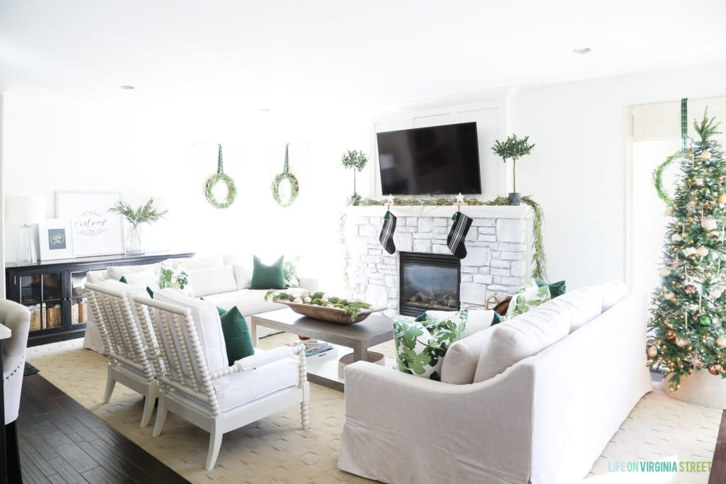 The same living room pained white with a white brick fireplace and white furniture and the room decorated for Christmas.