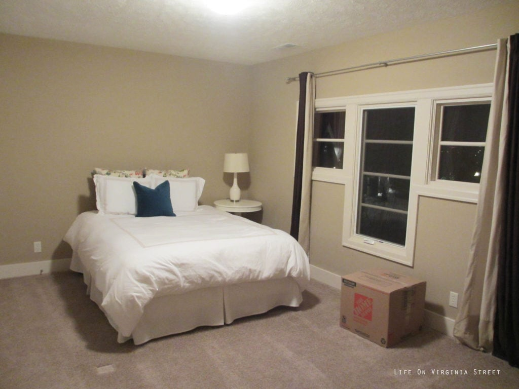 The guest bedroom with off white walls, and a small white bed.