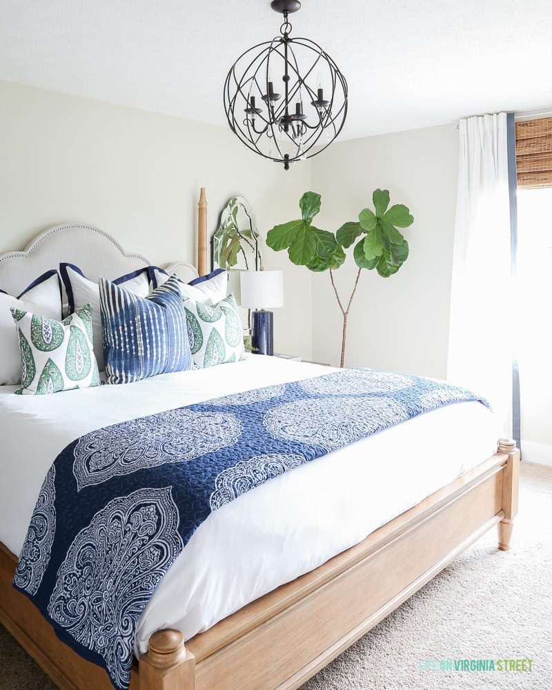 Bedroom with light gray walls, blue and white bedding, orb chandelier, natural woven shades and a fiddle leaf fig tree.