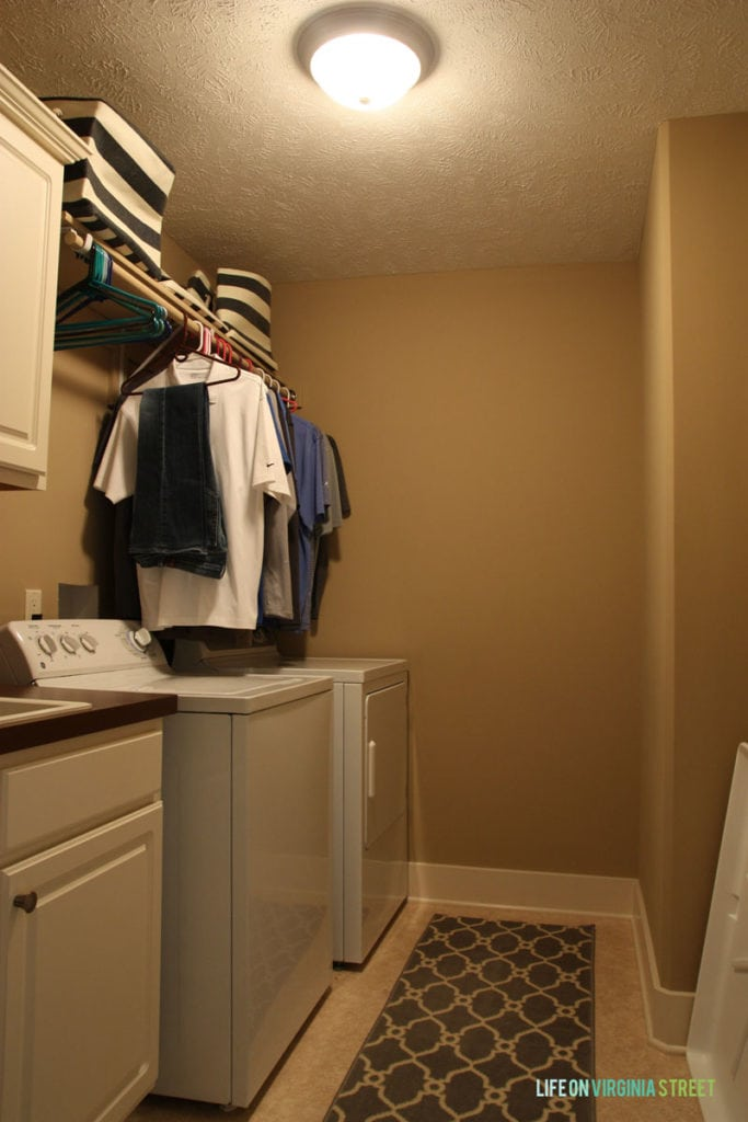 A dark beige laundry room with white washer and dryer.