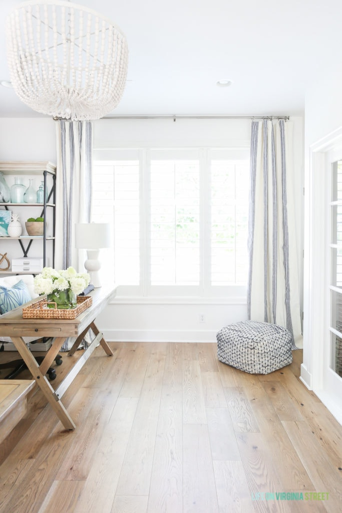 Home office with white oak hardwood floors, reclaimed wood desk, Benjamin Moore Simply White walls, blue and white striped drapes, and a white wood bead chandelier.