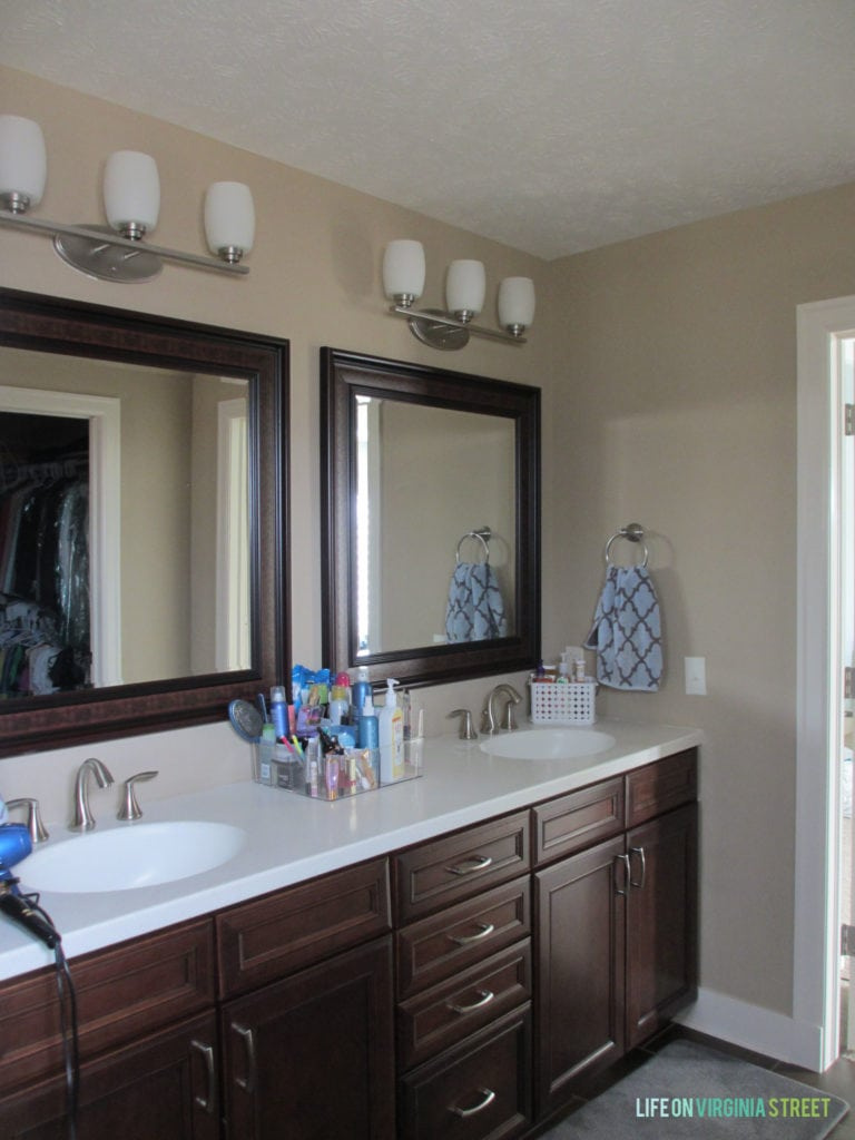 The master bathroom with a dark wood vanity and dark wooden mirrors.