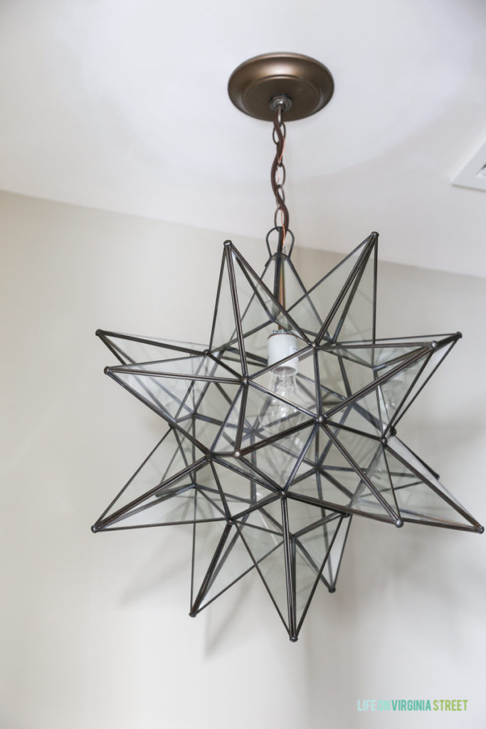 A star light fixture in a brushed metal hanging from the ceiling.