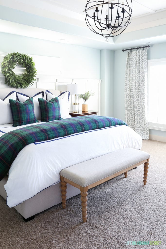 Bedroom with Sherwin Williams Sea Salt walls, white duvet cover, plaid comforter, orb chandelier and bayleaf wreath over bed.