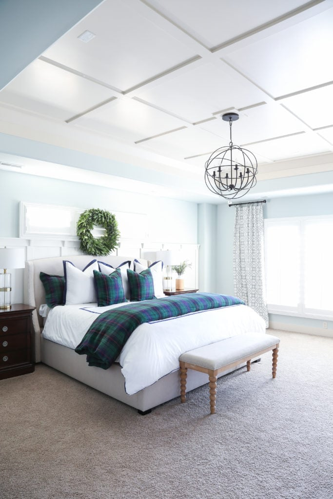 Christmas bedroom with Sherwin Williams Sea Salt walls, navy blue and green tartan bedding, board and batten trayed ceiling, and a fresh bay leaf wreath over the bed.