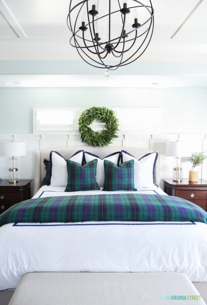 Christmas bedroom with fresh green wreath, white duvet, tartan bedding, and gold and glass lamps.