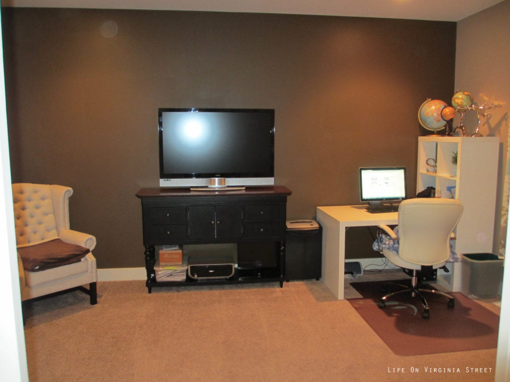 The office with dark brown walls, a small desk and armchair.  A dark room.