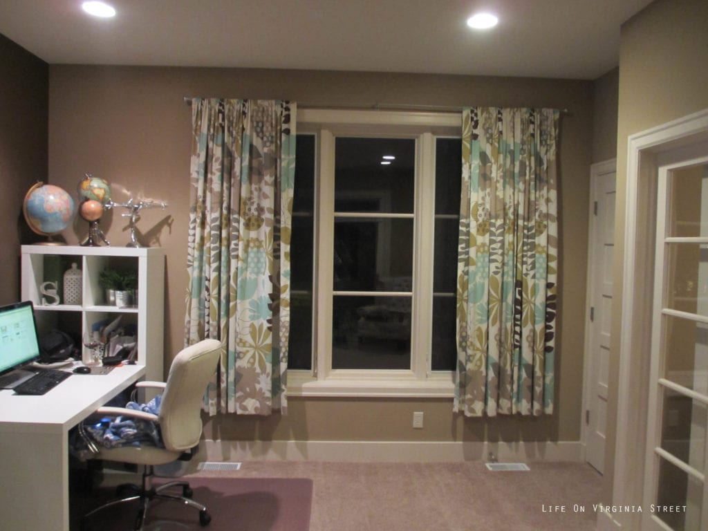 The office with a small white desk and floral curtains and beige walls.