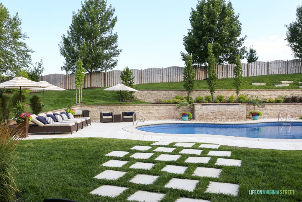 An in ground pool in the backyard with a large deck and chairs.