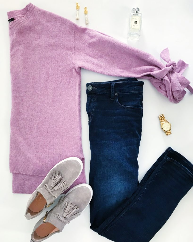 Soft pink purple sweater with tie-sleeves, dark denim skinny jeans, suede tassel sneakers, gold watch, gold and tassel earrings and Jo Malone perfume. The perfect outfit for late winter into early spring!