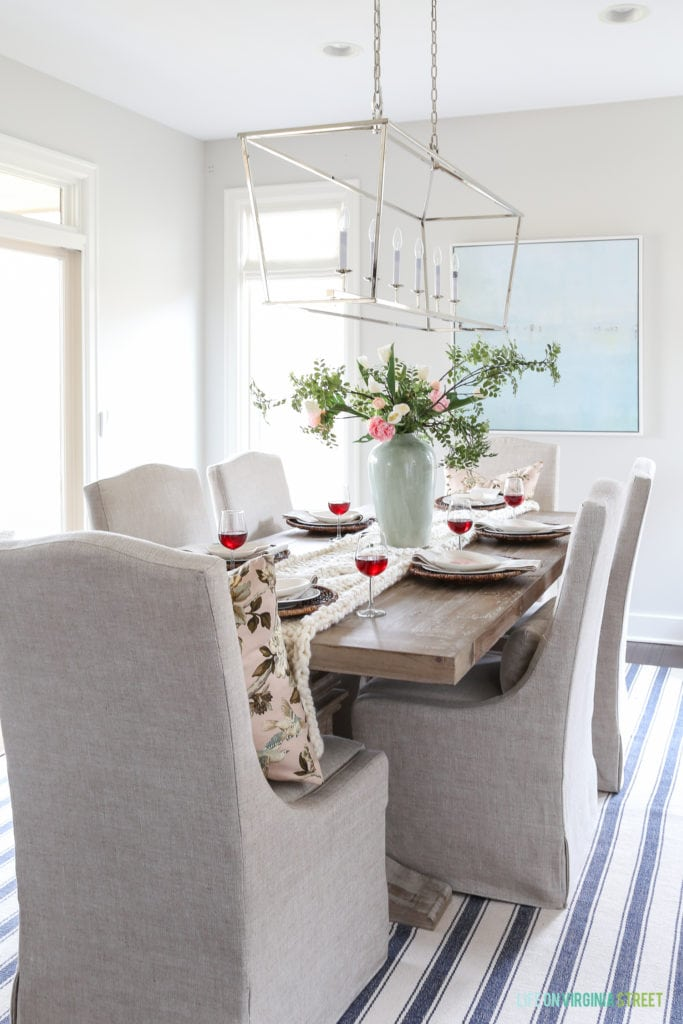 Neutral coastal dining room with a blush pink toned Valentine's Day tablescape.