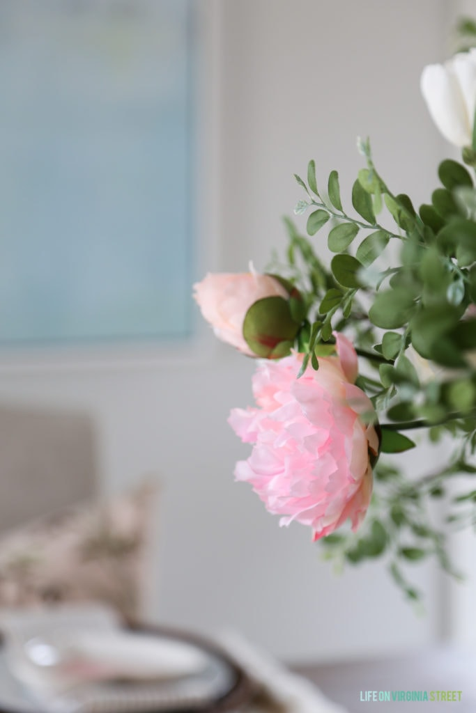 Faux blush pink peony stem in the middle of the table.
