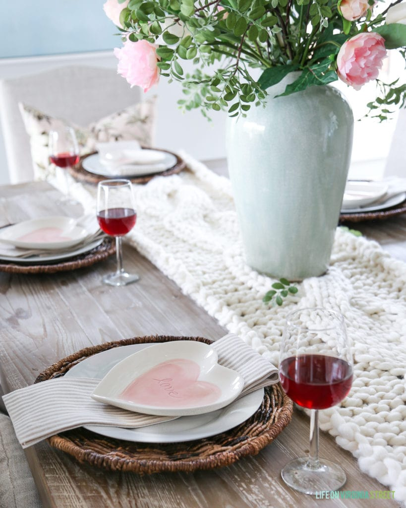 A Valentine's Day place setting on a reclaimed wood table, with celadon green vase, chunky knit table runner, and pink heart shaped plates.