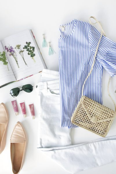 Spring outfit inspiration with blue and white striped ruffle sleeve blouse, white toothpick jeans, nude loafers, straw crossbody bag, aviator sunglasses, aqua tassel earrings and pink lip glosses.