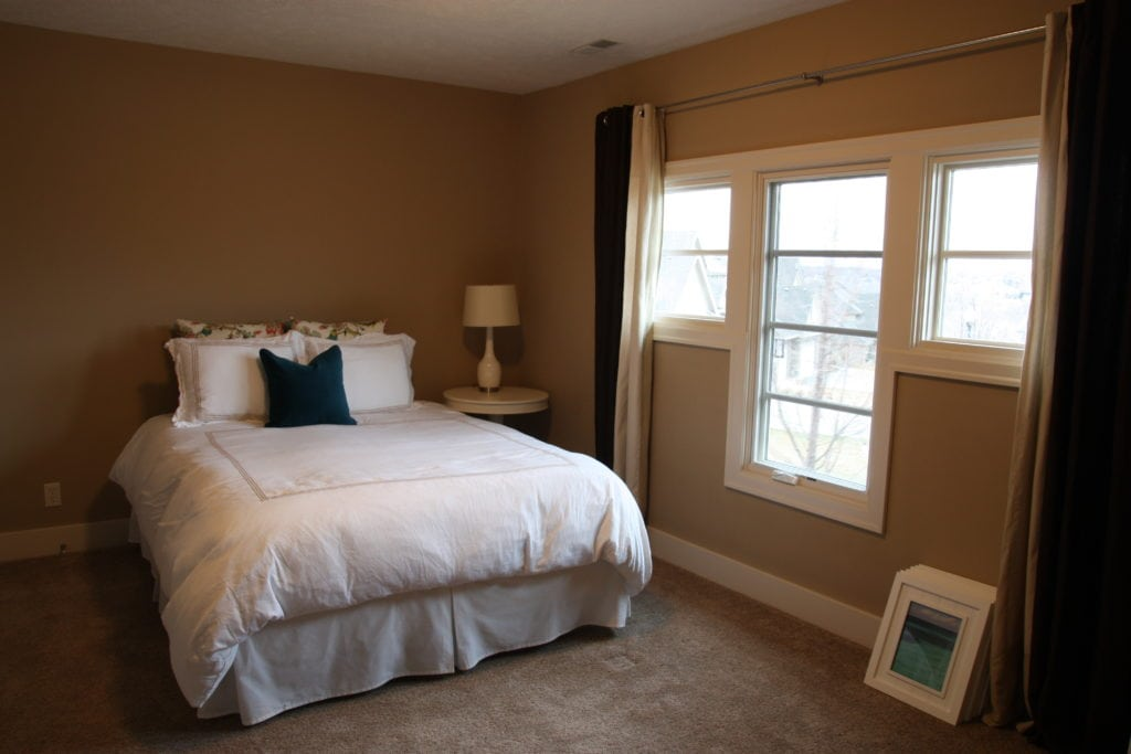 A guest bedroom with dark walls, a small bed with white bedding.