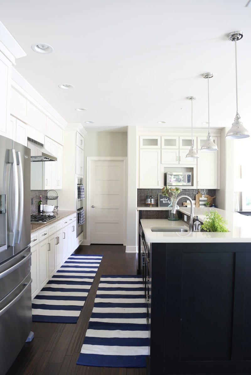 White Kitchen Cabinets with Black Island and Navy Striped Rug via ...