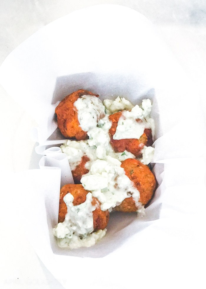 Chicken meatballs in a white container with a sauce covering it.