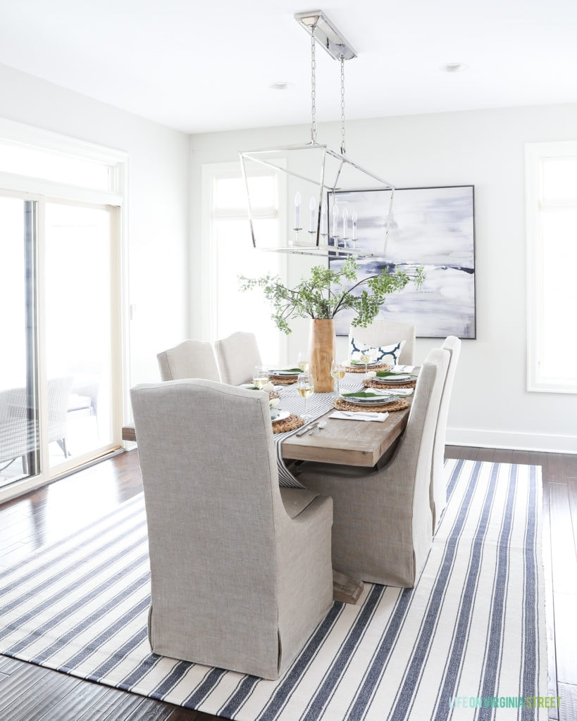 Dining room with Behr Silver Drop paint and navy blue and white accents. Linen chairs, reclaimed wood dining room table, navy blue striped rug, and Darlana linear pendant light fixture.