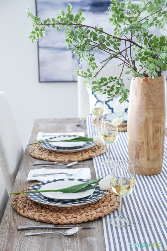 Navy blue and white gingham plates with seagrass chargers in an Easter tablescape.