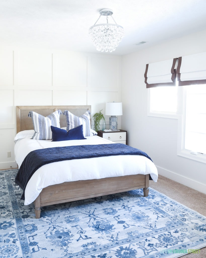 Coastal guest bedroom with blue rug, white-washed wood bed, white bedding, crystal chandelier and Benjamin Moore Classic Gray walls.