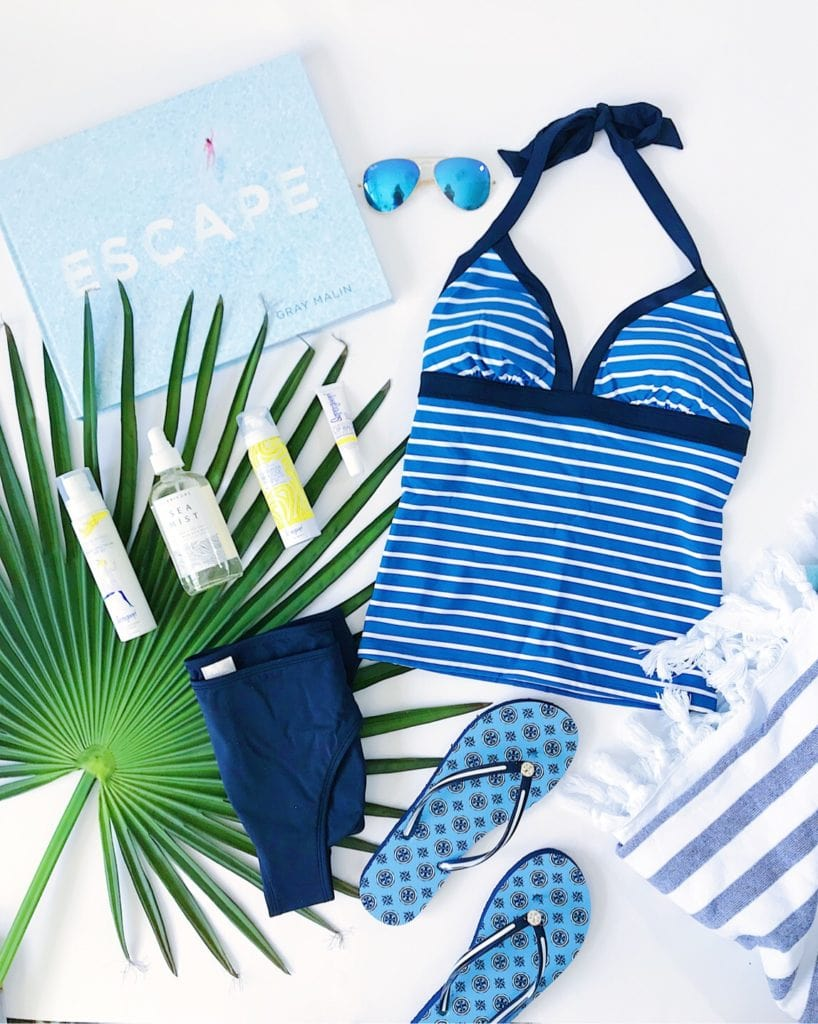 Blue striped tankini bathing suit, Tory Burch flip-flops, blue aviator sunglasses, and the best skin care products for the sun.