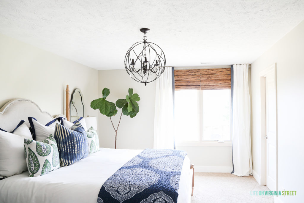 A white bedroom with a blue blanket on the bed, blue pillows and a large chandelier hanging above the bed.