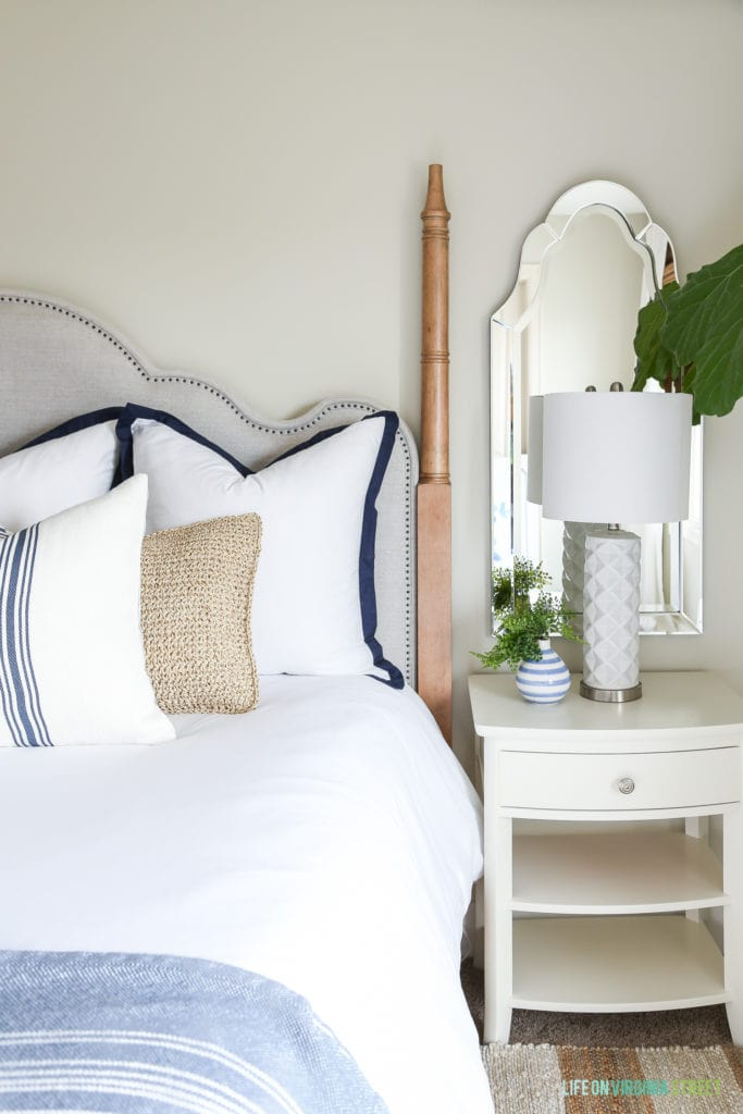 Off-white nightstands with an arched mirror and white textured lamp. White bedding is accented by blue and white striped pillows and a striped blanket.