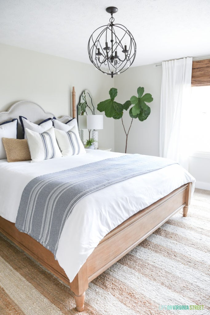 A coastal farmhouse style bedroom with a striped rug, orb chandelier, navy blue and white striped blanket, grainsack pillows and fiddle leaf fig tree.