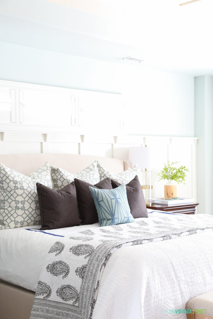 Tows of trellis pillows, and blue and green accents. Board and batten accent wall behind linen bed.