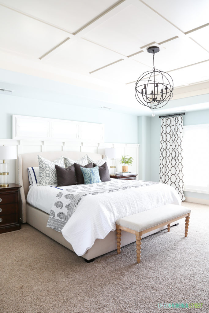 Bright master bedroom with board and batten ceiling and accent wall. Walls are painted Sherwin Williams Sea Salt. Beautiful white and brown paisley and scallop bedding from eBay. Trellis curtains accent blue and white bedding colors.