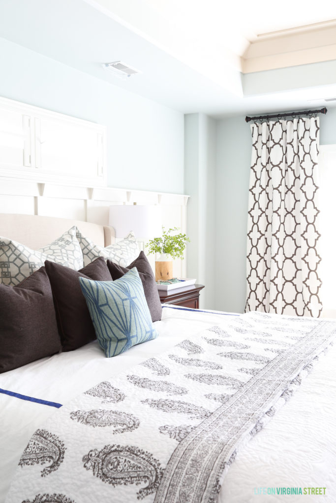 A large bed in the master bedroom with a side table and pillows on the bed.