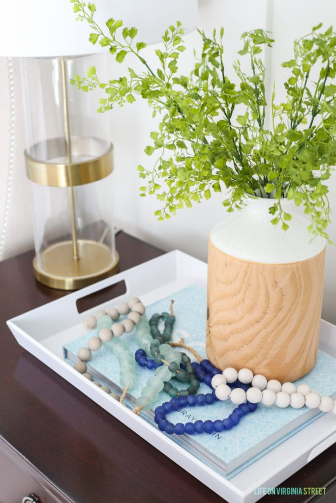 A tray with beads on a string in it plus a vase with greenery in it beside the bed.