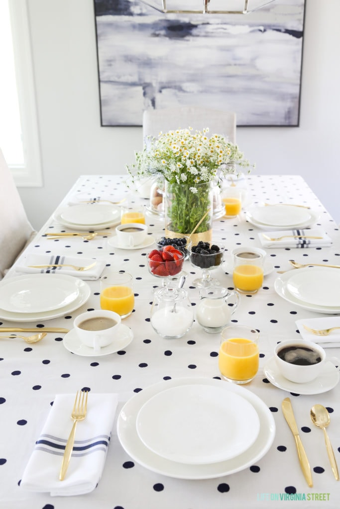 A brunch tablescape with a white and navy blue polka dot tablecloth.