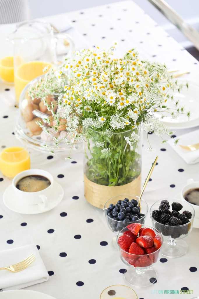 Baby's breath, daisy's, and berries on the table.