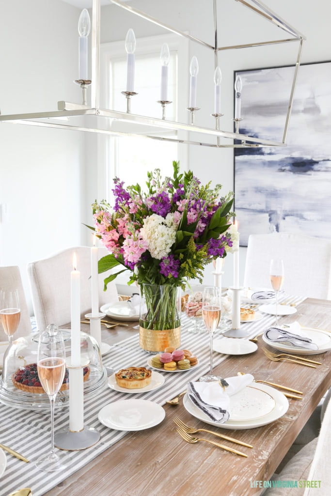 A gorgeous formal brunch tablescape, showcasing just how versatile the Olivia and Oliver dinnerware collection from Bed Bath & Beyond can be! I love the striped table runner, gold flatware, velvet-trimmed napkins, and long stemmed champagne glasses.