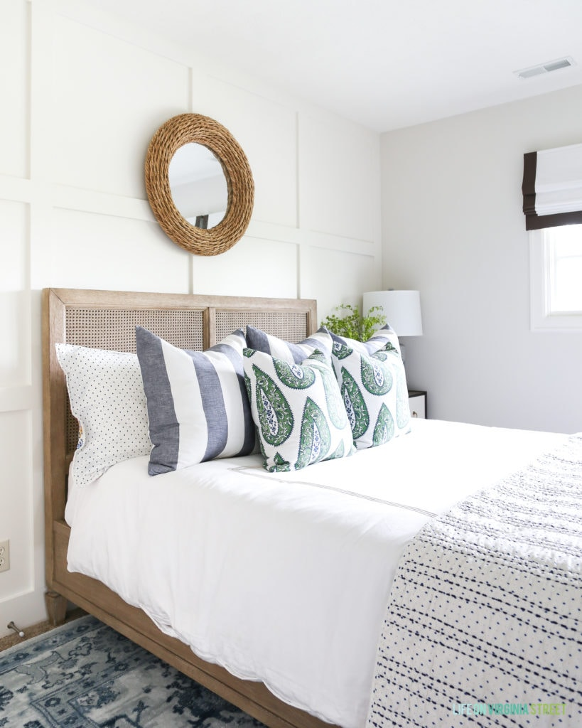 Coastal style bedroom with white linens, striped pillows, paisley accents, a woven rope mirror, board and batten wall and blue patterned rug.