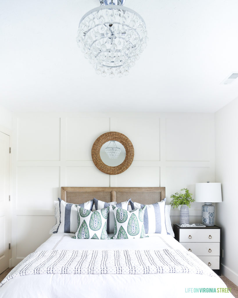 Summer guest bedroom with white board and batten grid wall, crystal chandelier, woven jute mirror, wood cane bed, blue and white striped pillows and green paisley throw pillows.