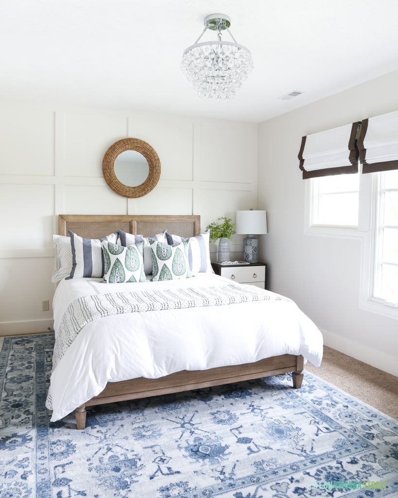 A beautiful bedroom with neutral base and blue and green accents. Includes a board and batten accent wall, jute rope mirror, wood cane bed from Pottery Barn, crystal flushmount chandelier, roman shades, and blue and green accents throughout.