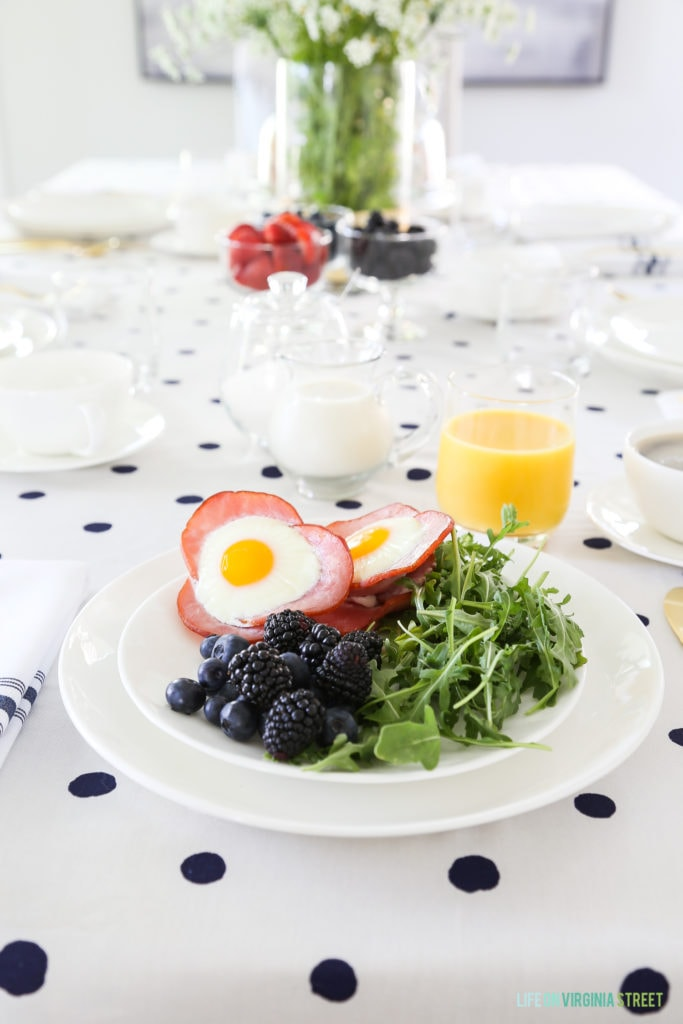 The plate of food with the eggs, bacon, berries and greens and a glass of orange juice on a polka dotted tablecloth.