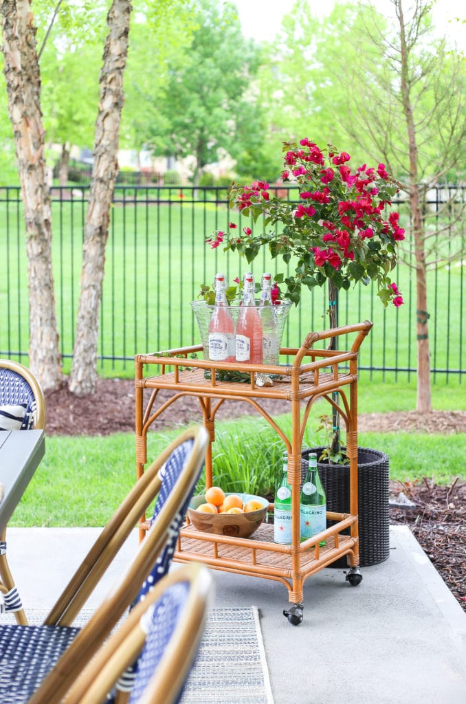 Outdoor rattan barcart with drink station and bougainvillea.