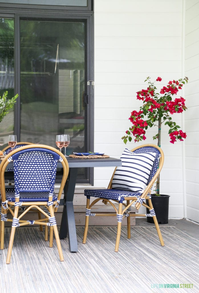 Dreamy outdoor dining space with blue and white bistro chairs, striped pillows, a neutral rug, and bougainvillea.