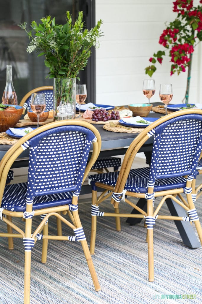 Beautiful outdoor dining area with navy blue and white bistro chairs, wood x-leg table, and colorful accents.