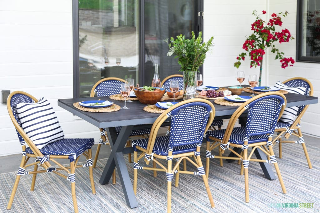 Outdoor dining space with bistro chairs and blue and white accents.