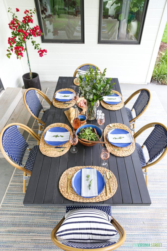 Outdoor dining tablescape with navy blue and white bistro chairs, wood table, striped pillow, seagrass chargers, blue melamine plates and wood accents.
