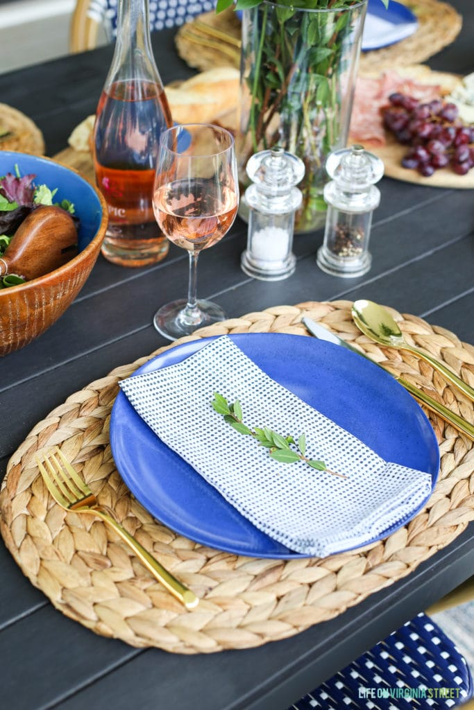 Outdoor place setting with a coastal vibe. Includes seagrass chargers, blue plates, dot stripe napkins and gold flatware.