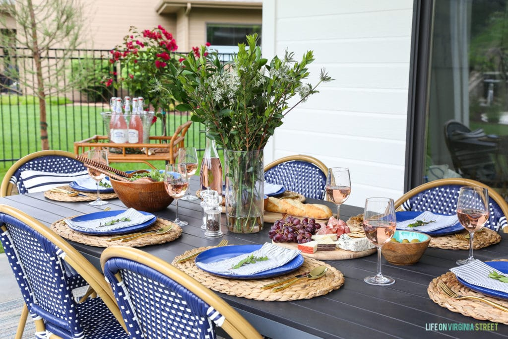 An outdoor dining tablescape with seagrass chargers, indigo blue melamine plates, gold flatware and greenery.