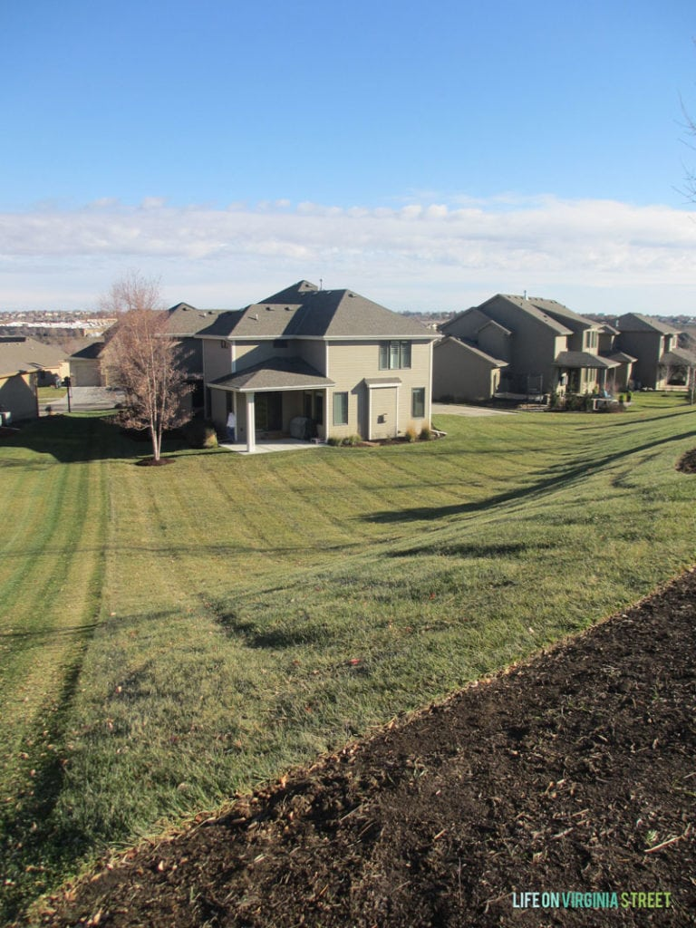 Light brown houses in a row with grass.