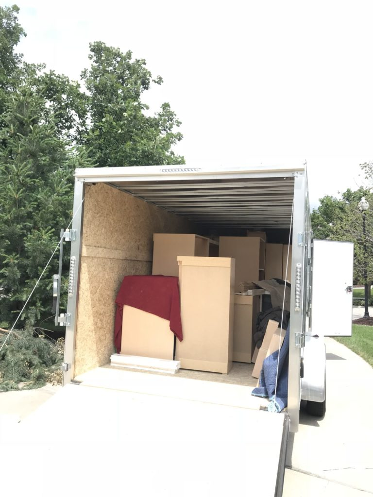 A delivery truck with the door opened in the back and boxes stacked up.