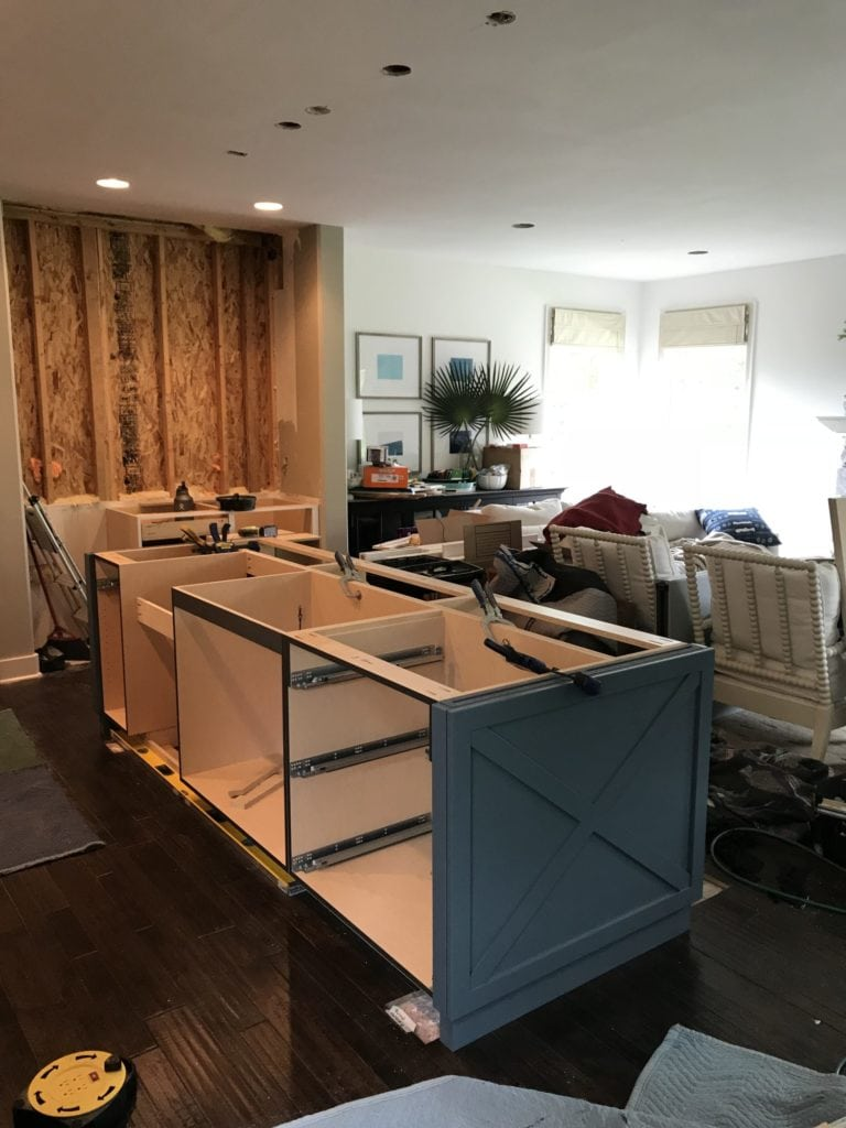 Putting together the kitchen island that is navy blue.
