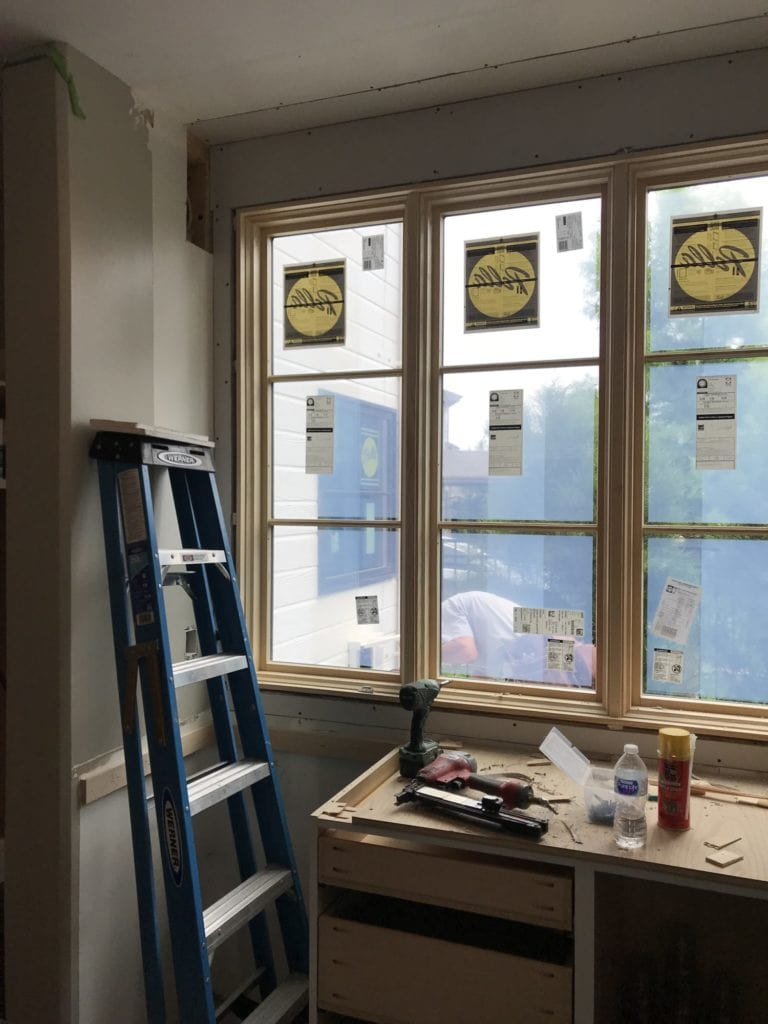 A step ladder beside the newly installed window in the kitchen.